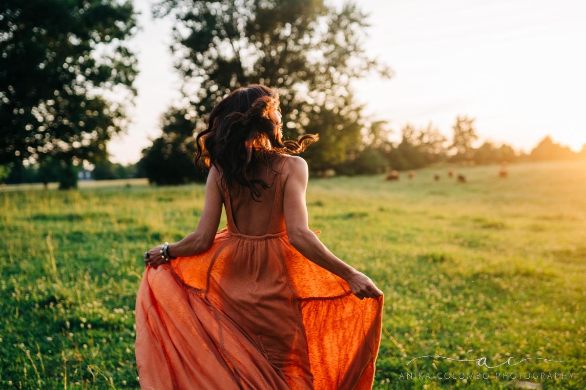 woman running through a field at sunset