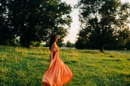 woman walking in a field at sunset