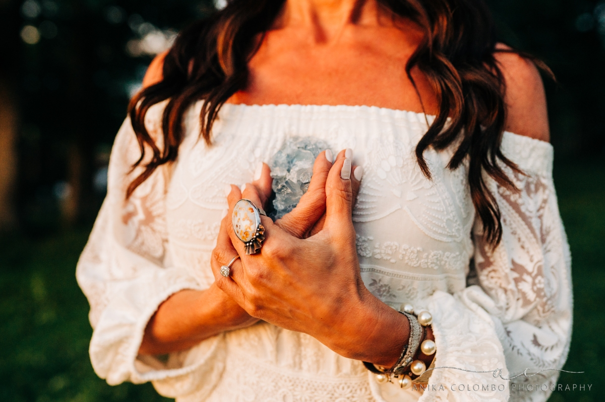 woman in off shoulder dress holding a crystal to her chest with lots of chunky vintage jewelry
