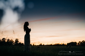 silhouette of a woman in a yoga pose in a field at sunset