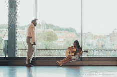 woman playing a guitar in mainstreet station in front of big windows overlooking the city while a man looks on leaning on the window holding music sheets
