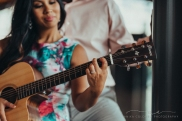couple embracing as they play a guitar together