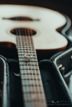 photo of a guitar with an engagement ring sitting on the strings