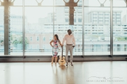 couple standing in front of a big window at mainstreet train station in richmond va looking in opposite directions and both holding a guitar upright on the ground