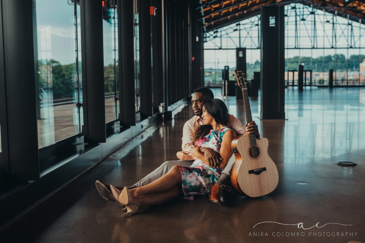 couple sitting on the floor of mainstreet train station in richmond va embracing and holding a guitar